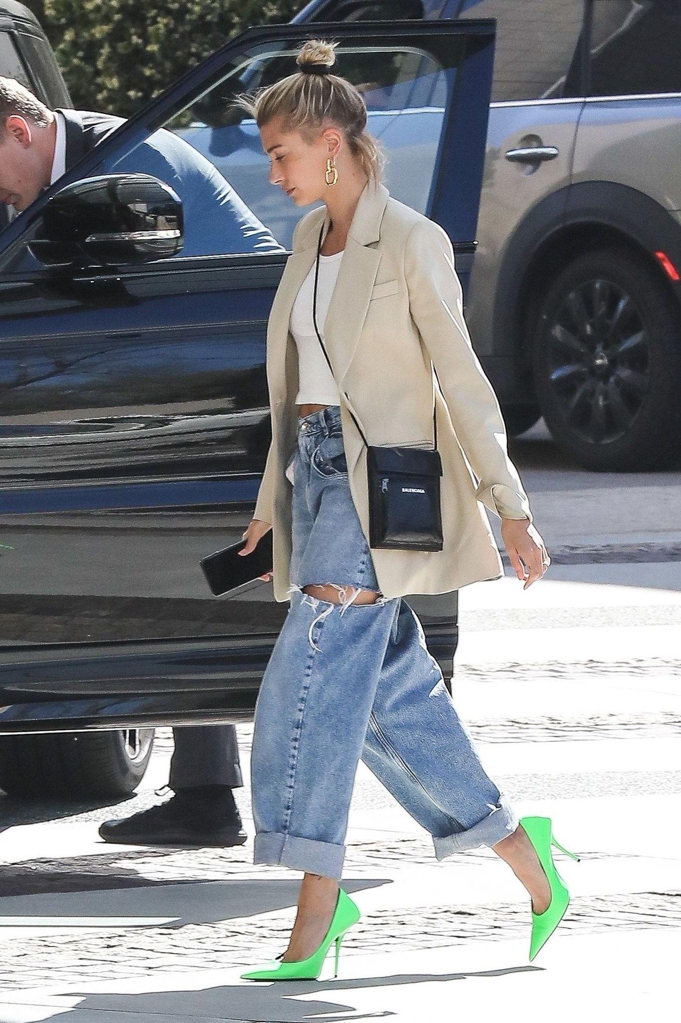 Hailey Bieber mặc quần jeans rách, áo blazer và mang giày cao gót xanh neon