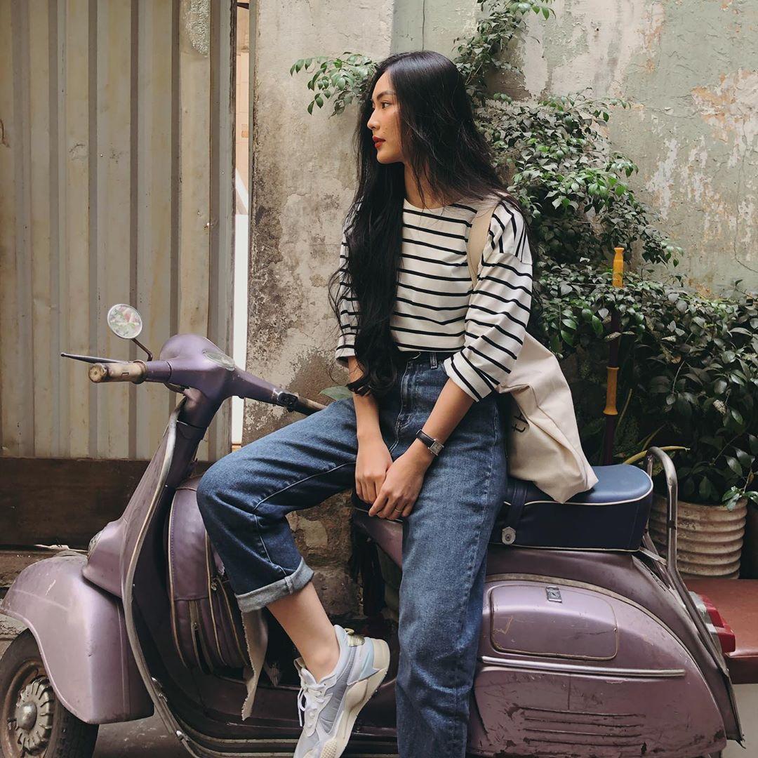 Helly Tống mặc áo sọc quần jeans, ngồi trên Vespa