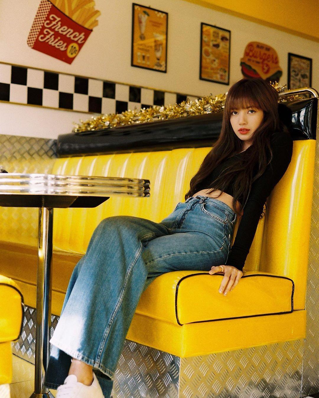 Lisa mặc quần jeans ống rộng và áo crop-top đen