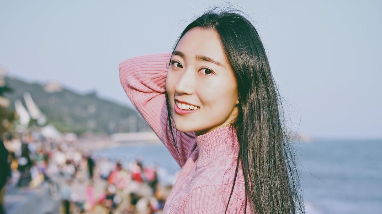 chăm sóc da cô gái tóc dài áo hồng bên bãi biển