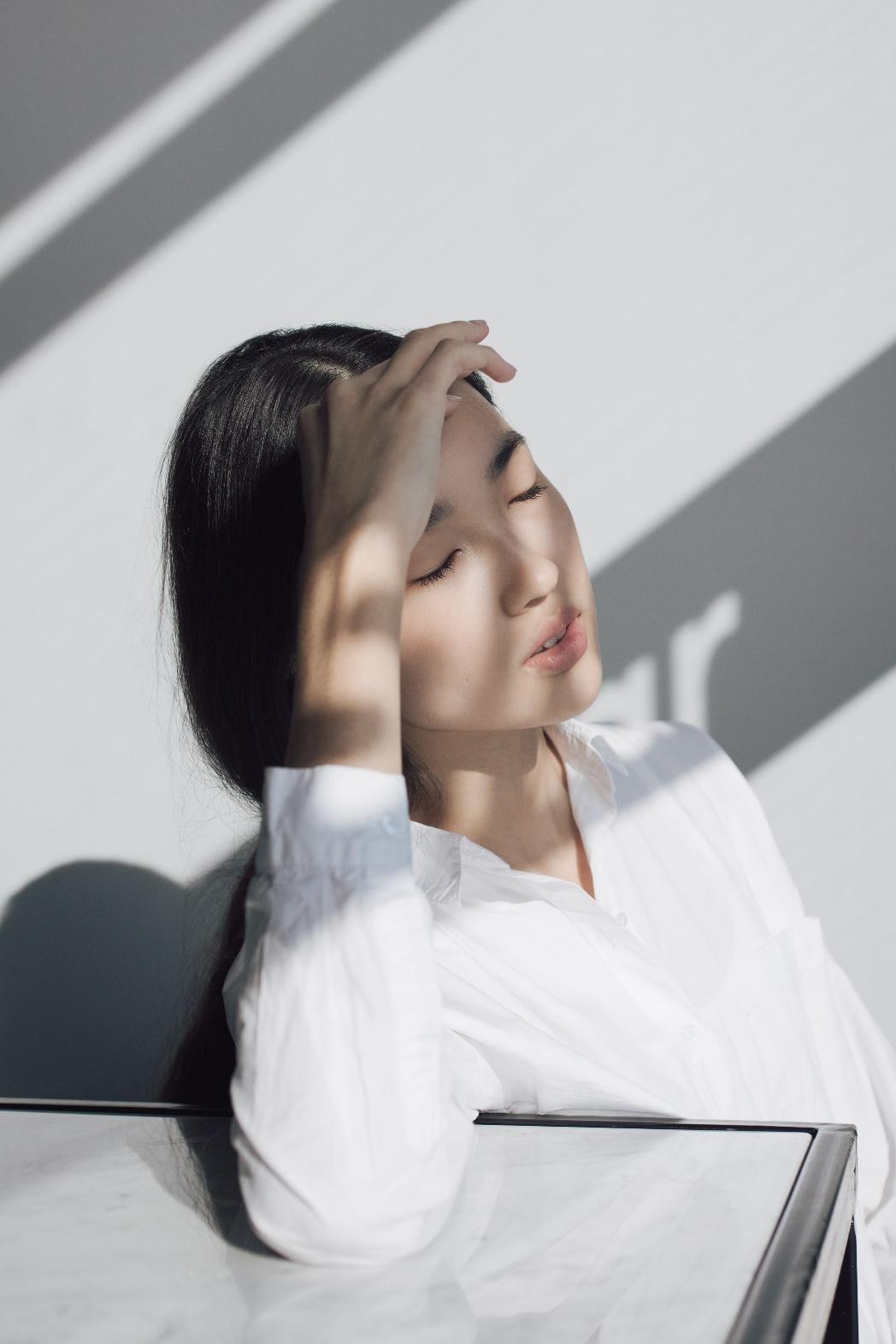 chăm sóc da cô gái tóc đen dài mặc áo sơmi trắng