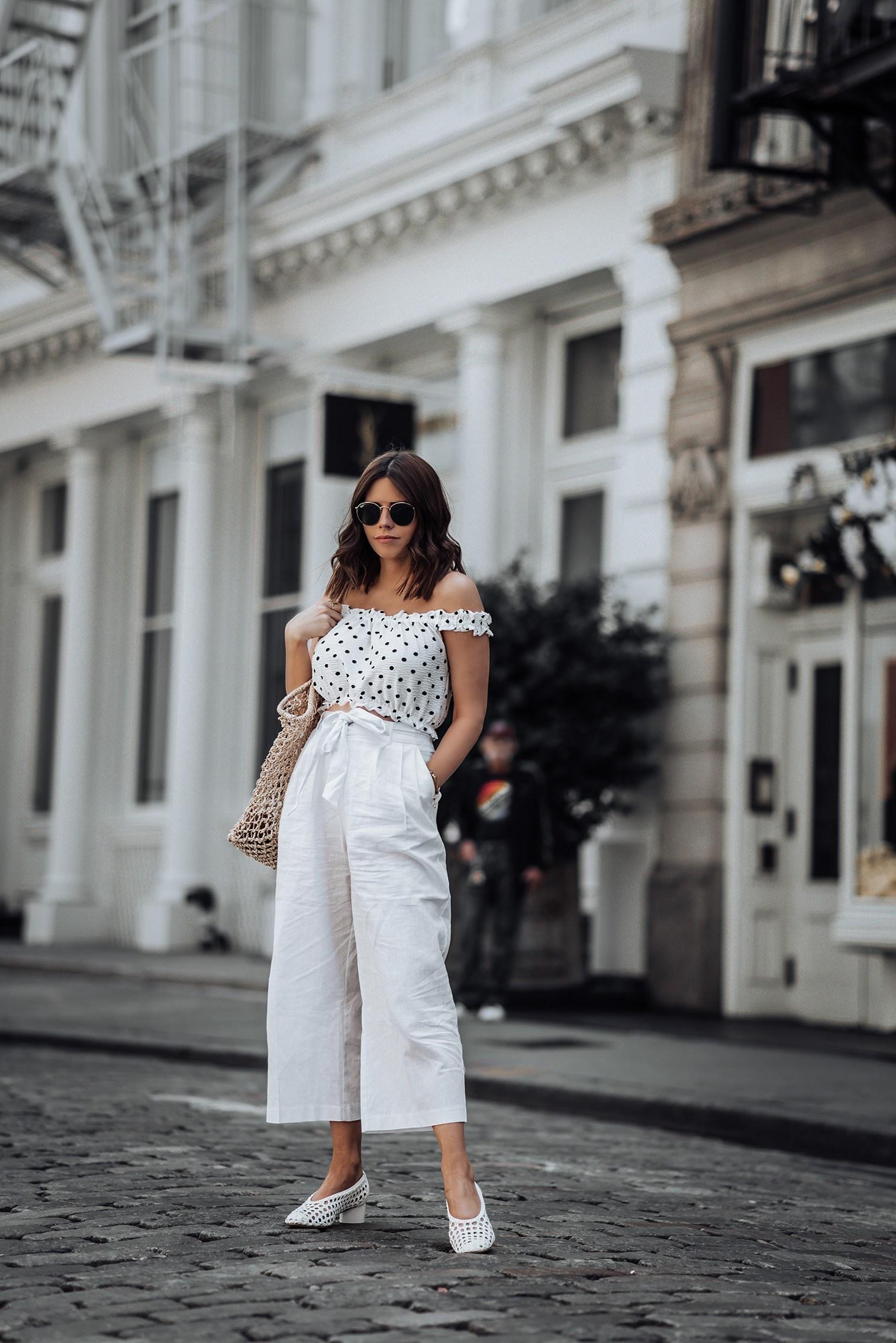 Cô gái mặc áo trễ vai chấm bi và quần baggy đũi màu trắng