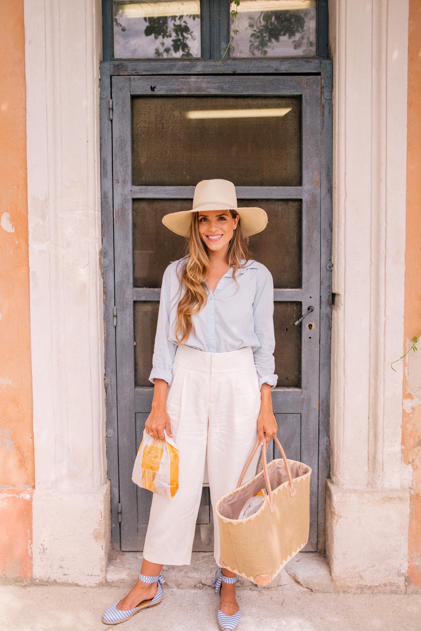 Cô gái mặc áo sơ mi xanh, quần baggy trắng, đội mũ cói, xách túi cói