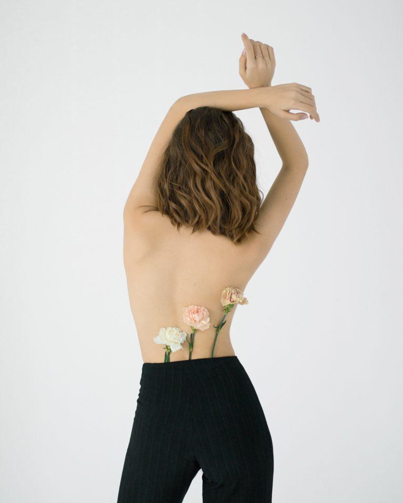 Cách trị mụn-Cô gái cài hoa ở lưng.