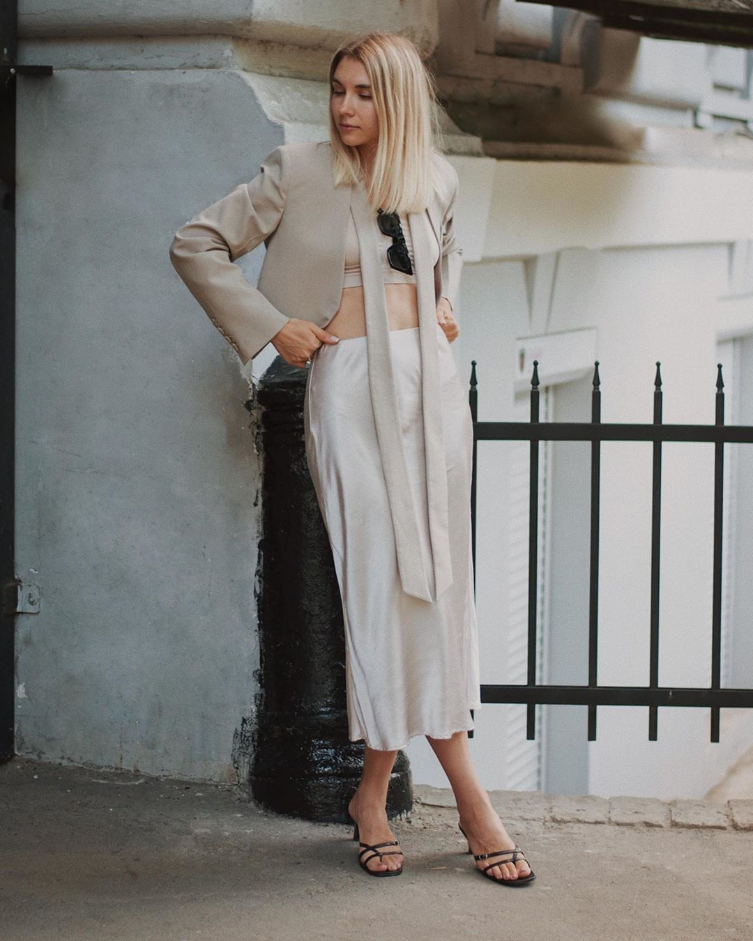 Cô gái mặc chân váy suông màu trắng cùng áo crop-top và blazer