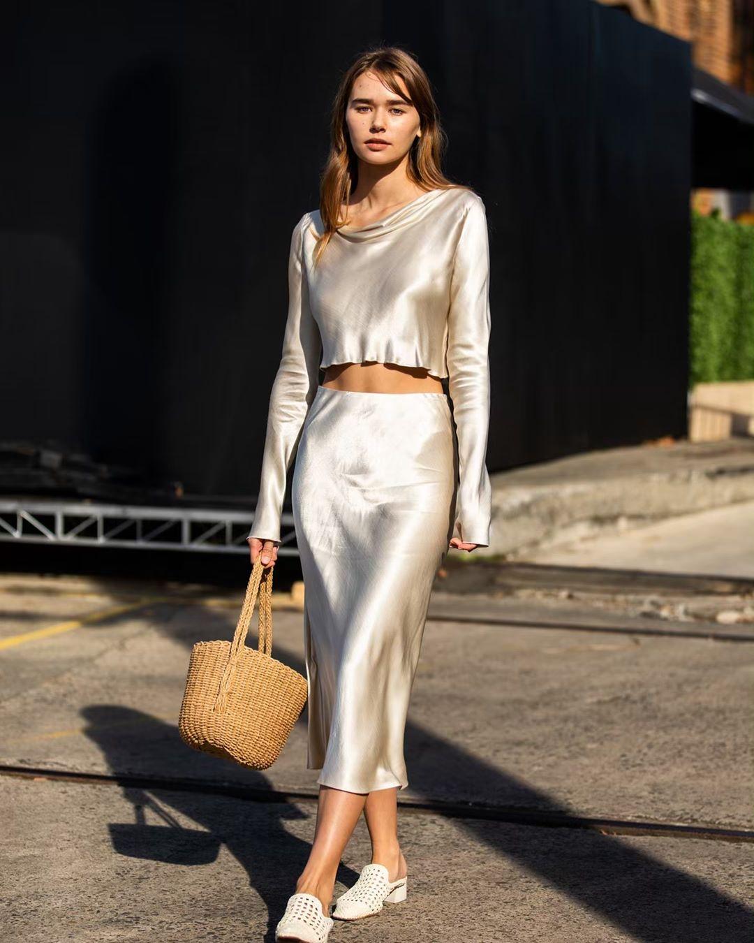 Fahionista mặc áo và chân váy suông vải satin màu trắng