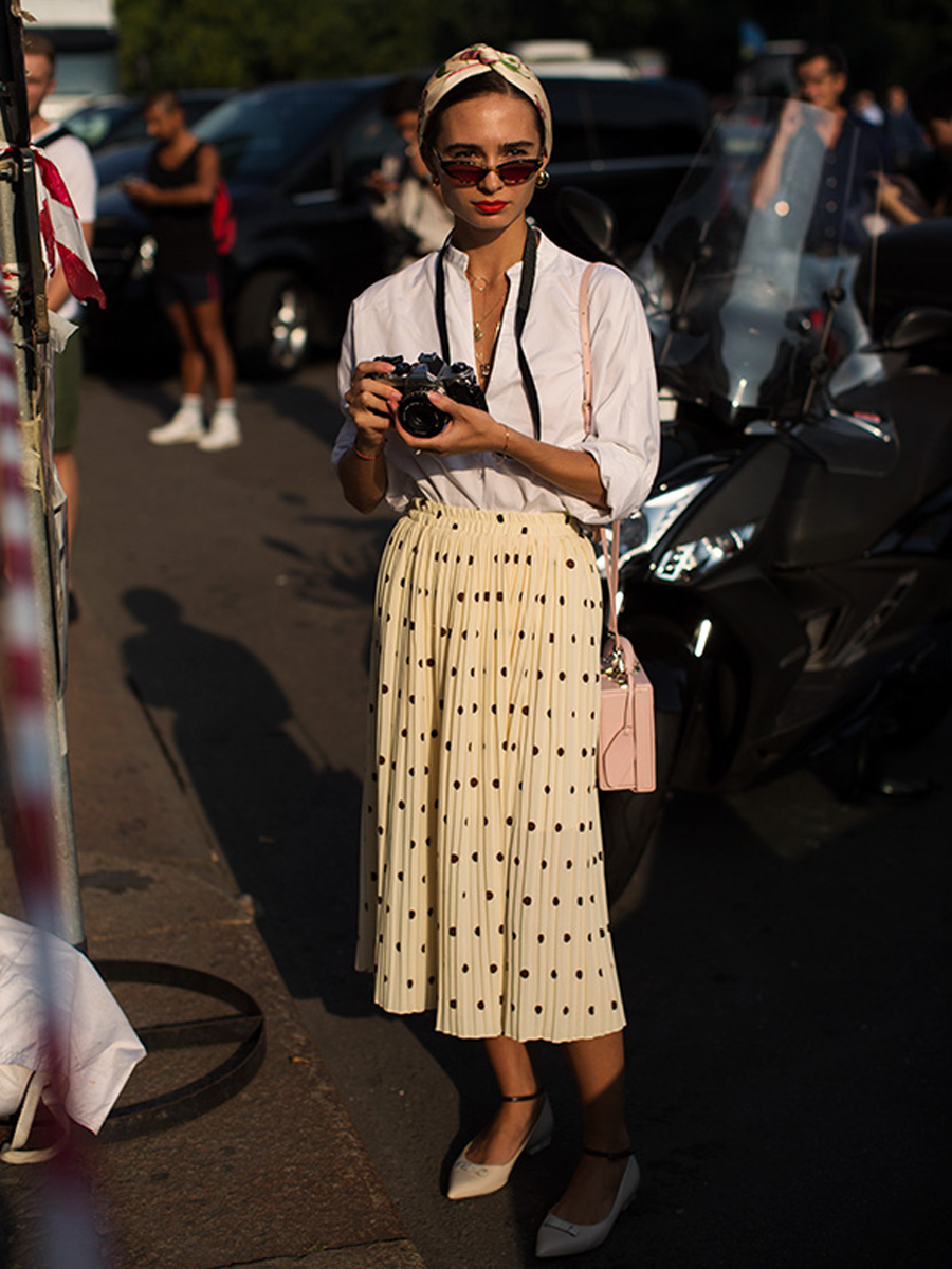 Cô gái mặc áo sơ mi trắng và chân váy suông xếp ly chấm bi