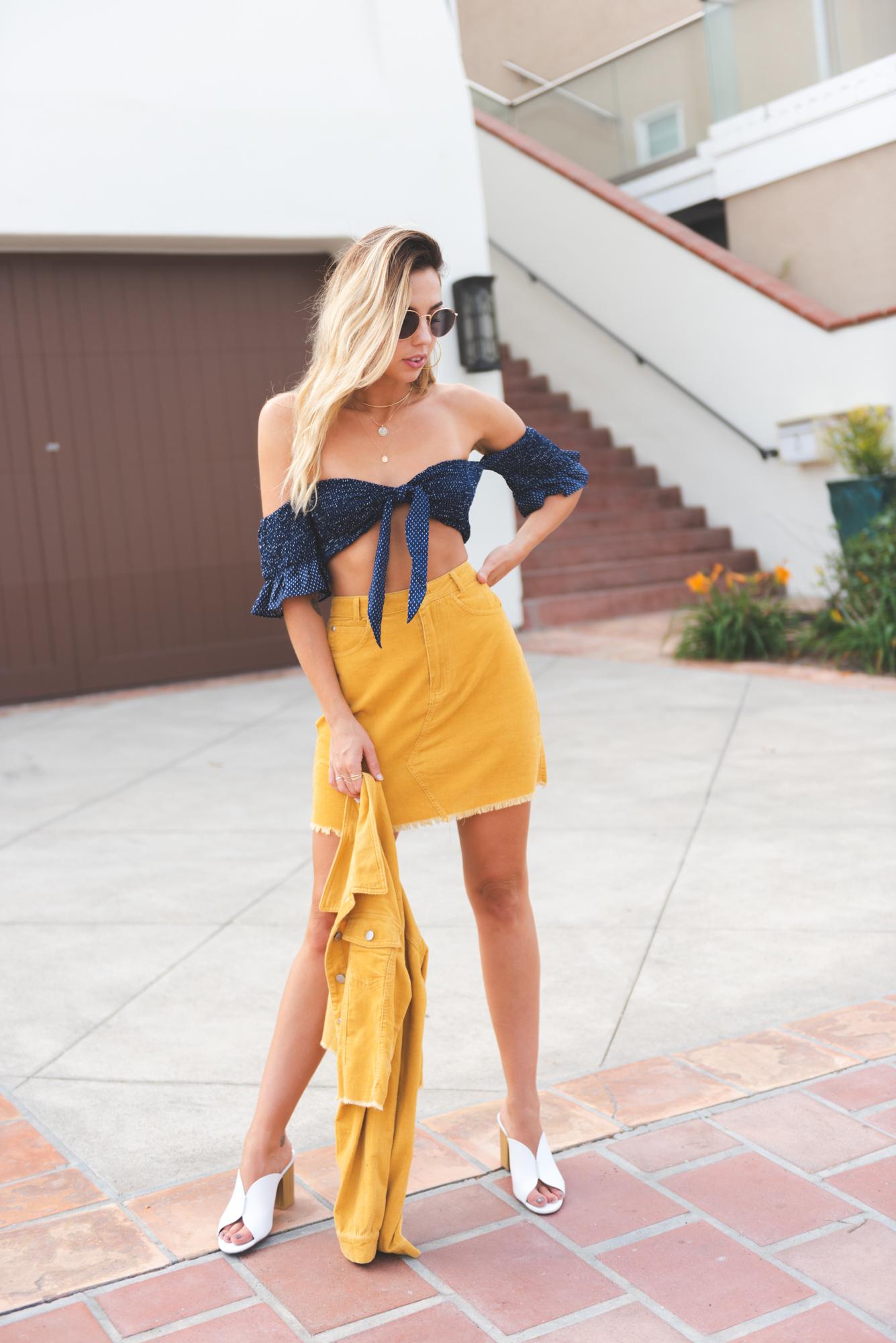 fashionista mặc chân váy vàng và áo xanh đậm