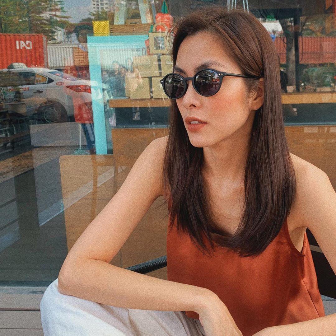 Tăng Thanh Hà mặc áo hai dây màu cam đất, đeo kính đen