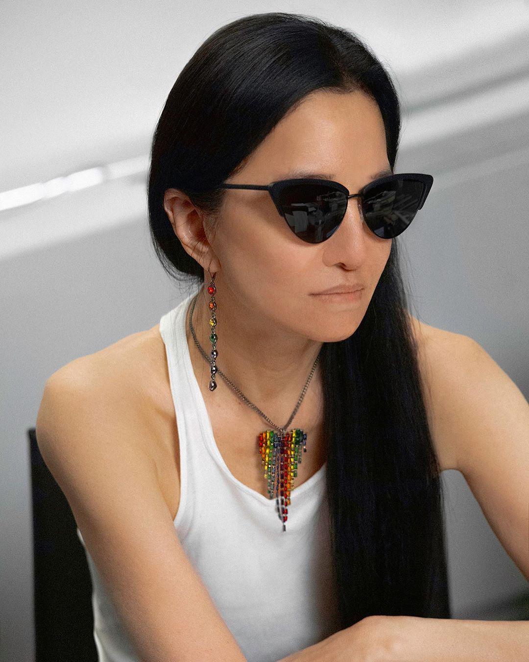 NTK Vera Wang đeo kính đen, mặc áo tank top trắng