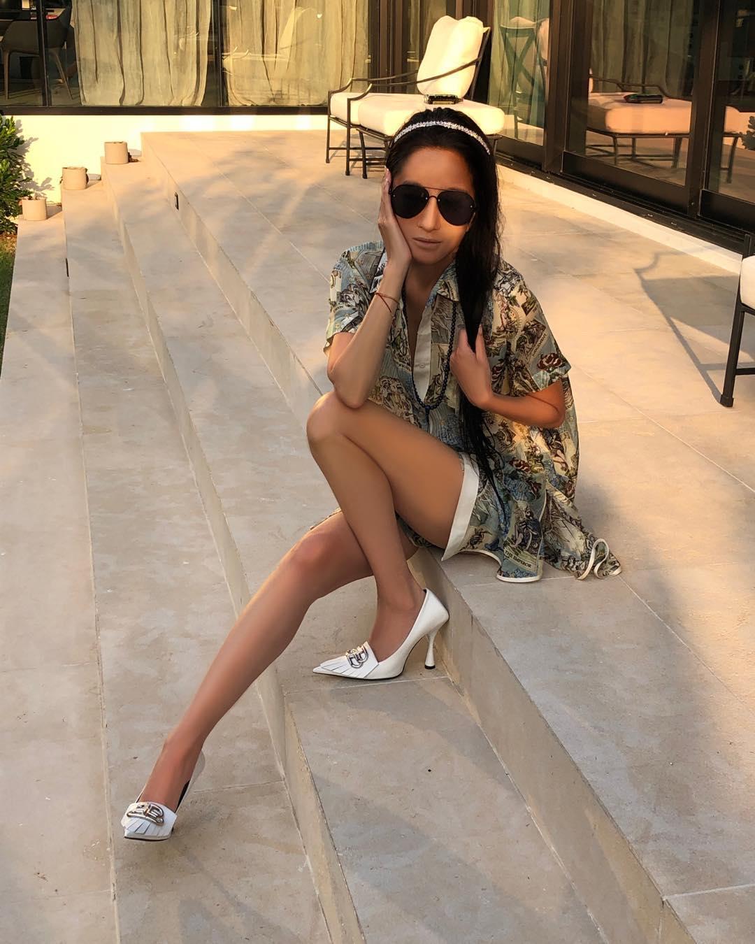 NTK Vera Wang mặc áo sơ mi họa tiết và mang giày cao gót trắng