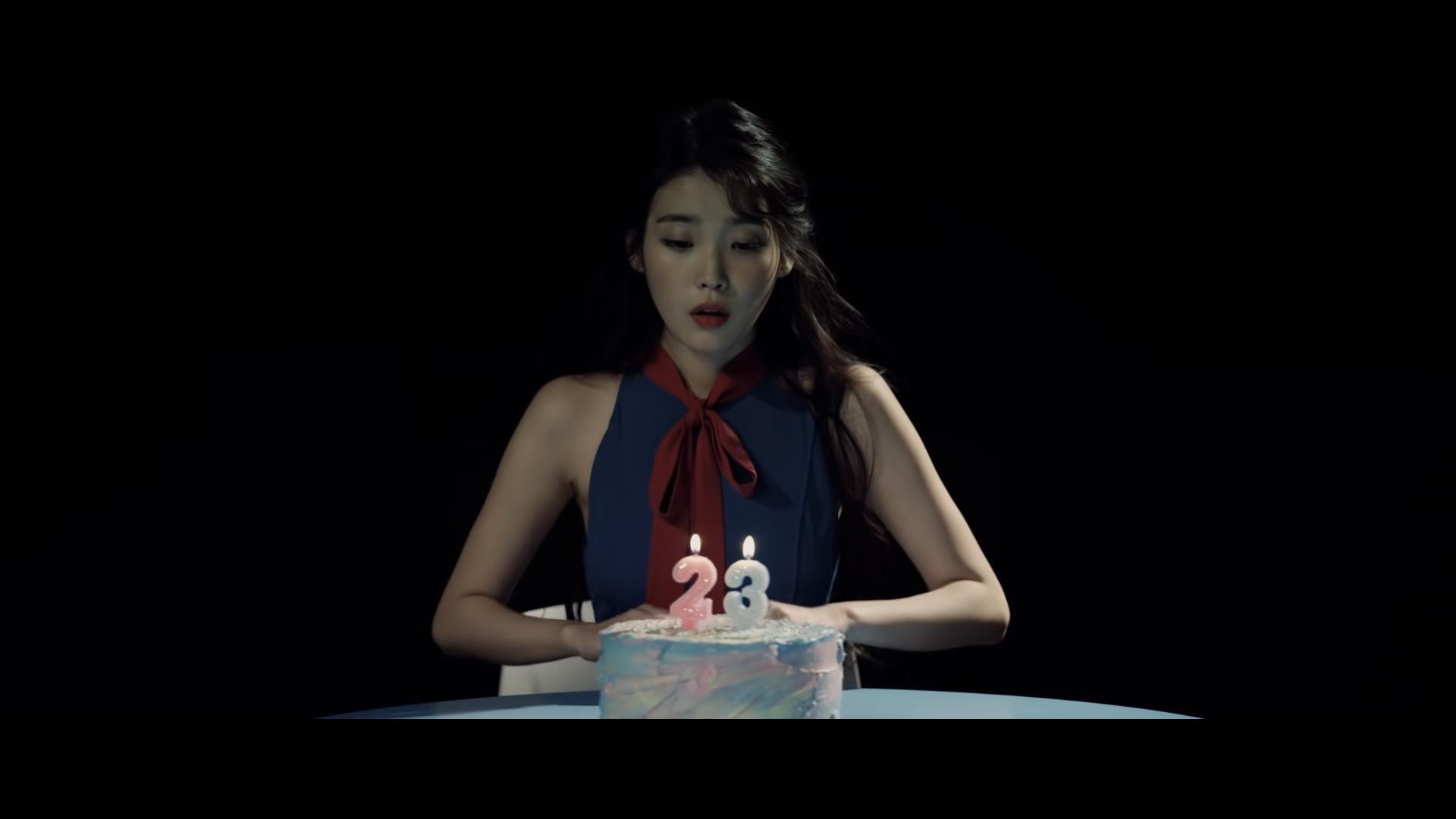 Ca sĩ IU mặc đầm xanh thắt nơ đỏ trong MV 23