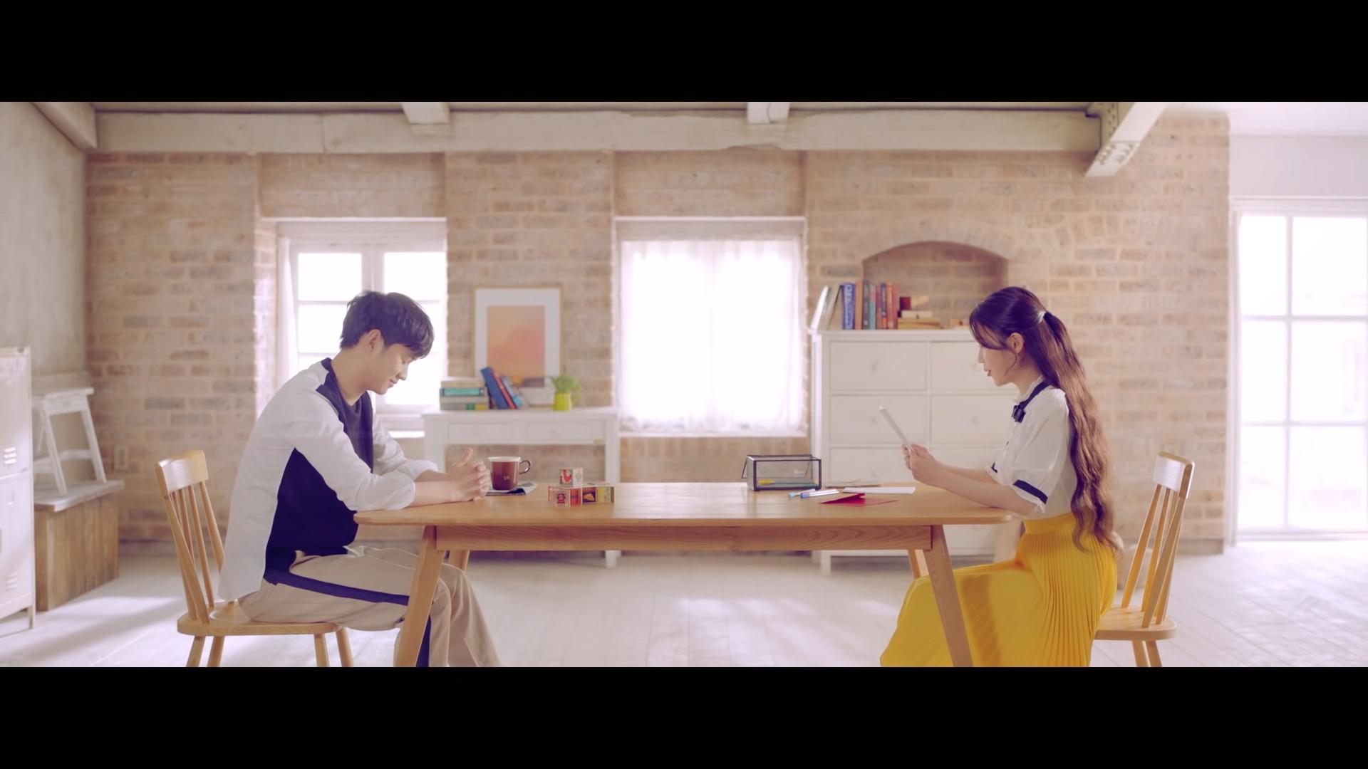 ca sĩ IU mặc áo sơ mi trắng, chân váy xếp ly vàng trong mv ending scene