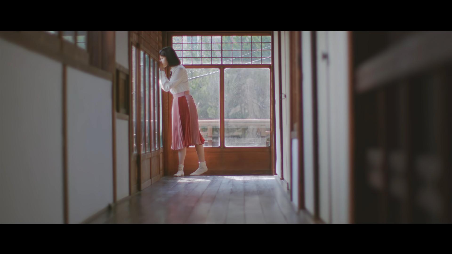 ca sĩ IU mặc áo sơ mi trắng và chân váy xếp ly trong MV Through The Night