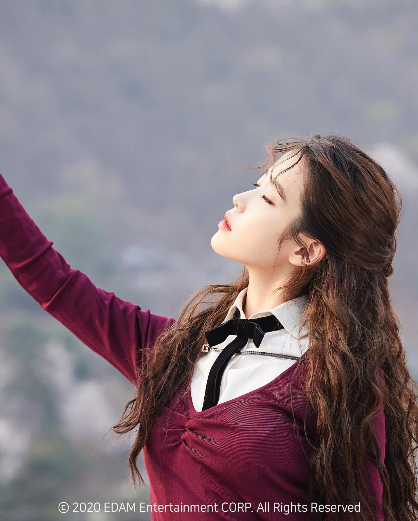 ca sĩ IU mặc áo len tím, thắt nơ đen trong mv eight