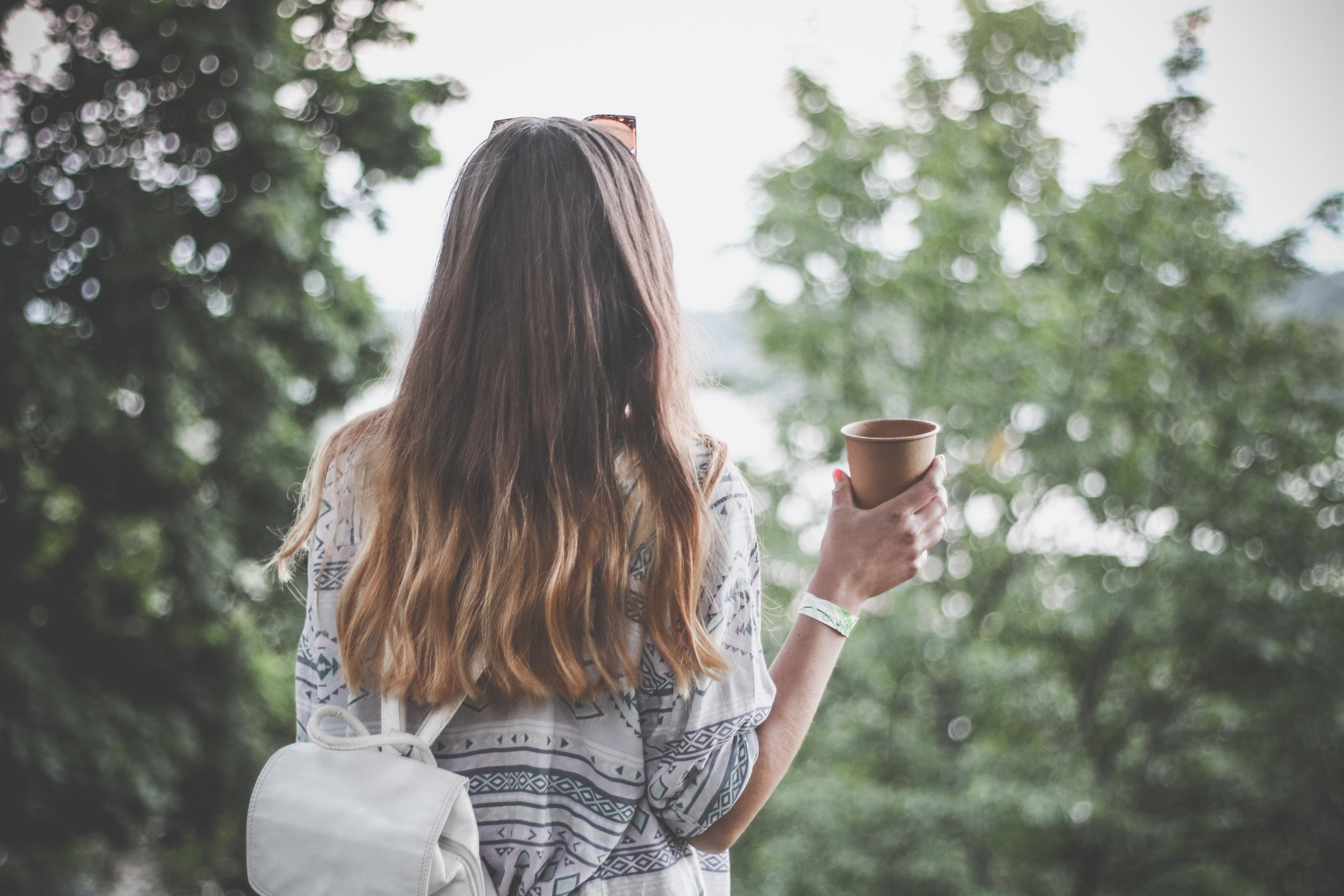 cô gái cầm ly cà phê