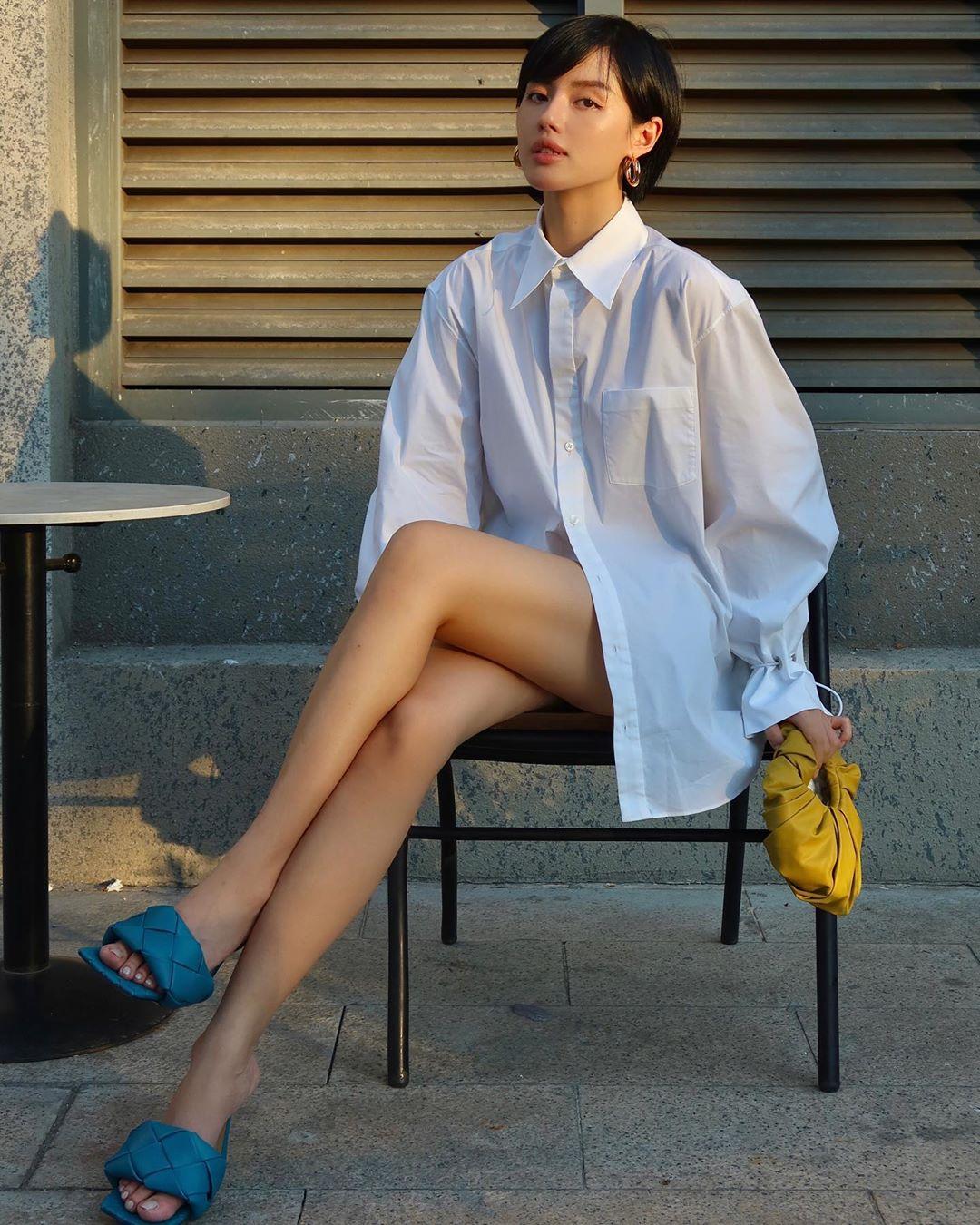 Khánh Linh mang giày mules mũi vuông màu xanh, mặc áo sơ mi trắng oversized