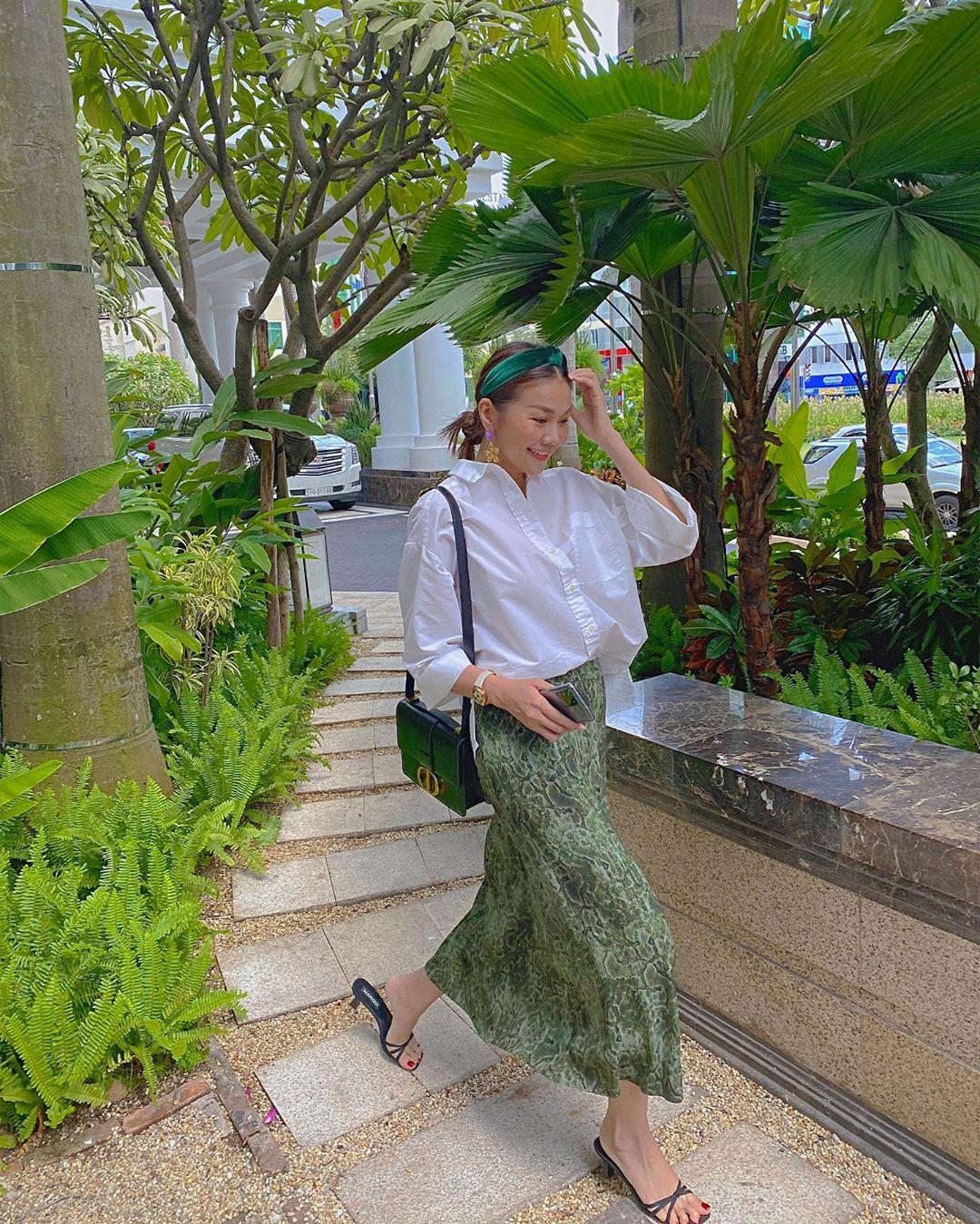 Siêu mẫu Thanh Hằng mang giày mules dây đen, váy suông xanh lá, sơ mi trắng