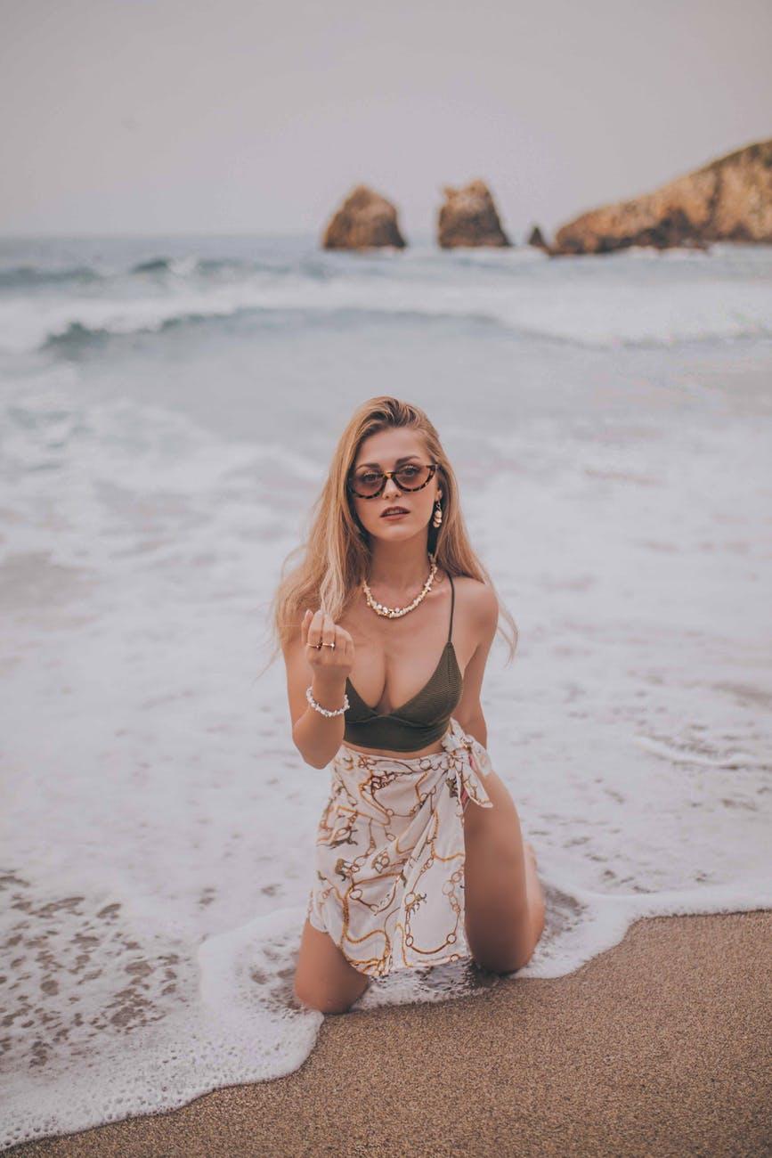 Tẩy tế bào chết-Cô gái quỳ trên bãi biển.