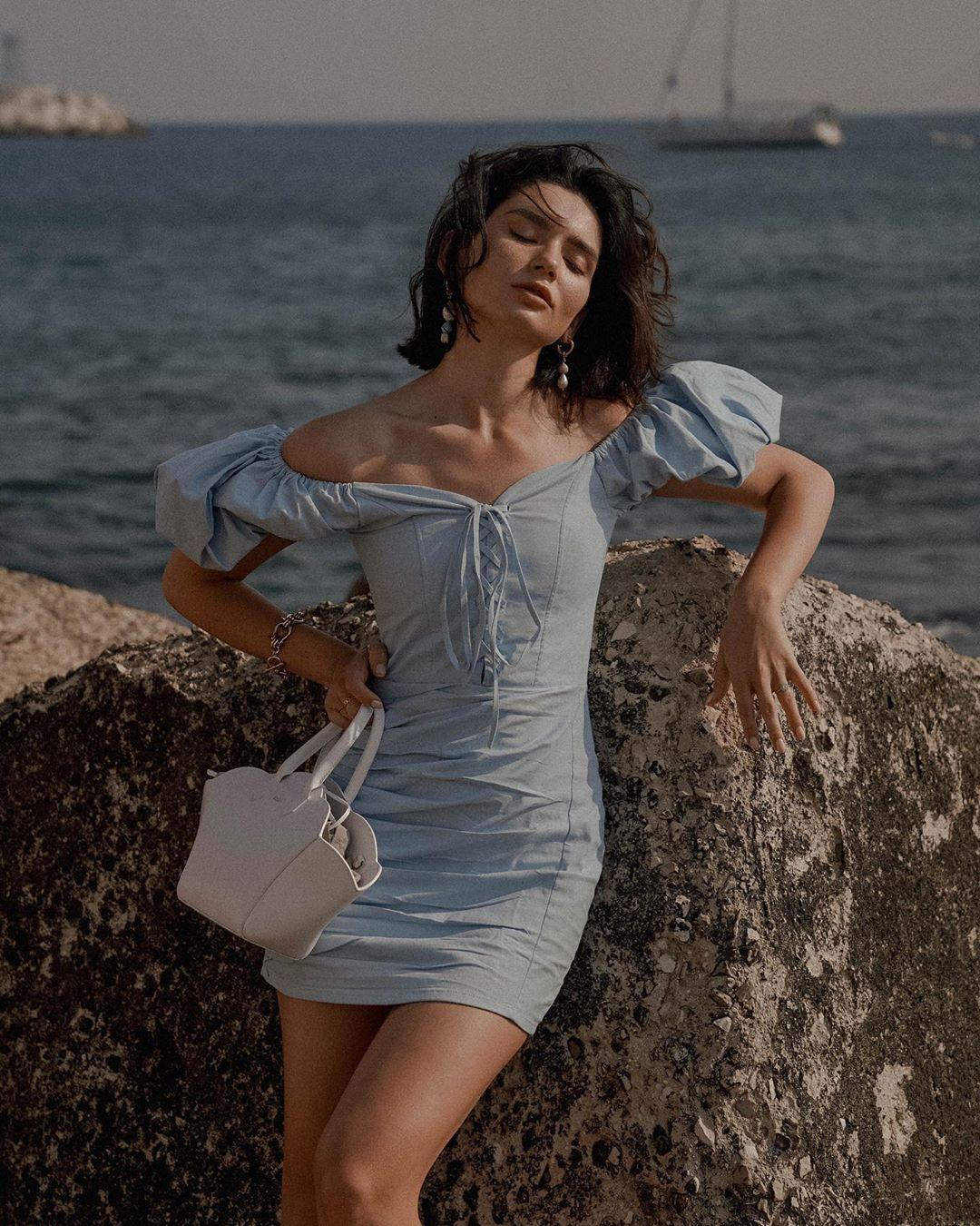 Váy trễ vai đi biển ngắn ôm sát màu xanh da trời, túi xách màu trắng