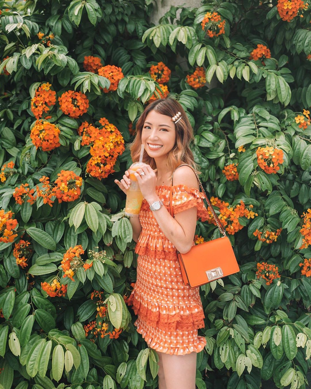 Váy trễ vai ngắn ôm sát nhún bèo màu cam, túi xách cam