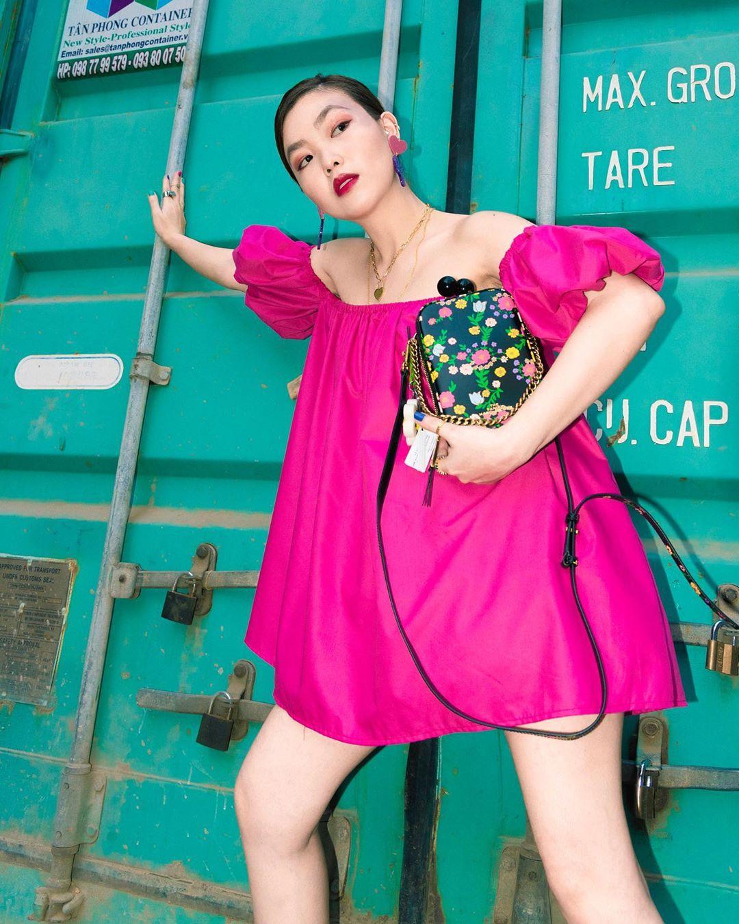 VJ Kaylee mặc váy trễ vai phom rộng màu hồng tía, cầm túi xách họa tiết