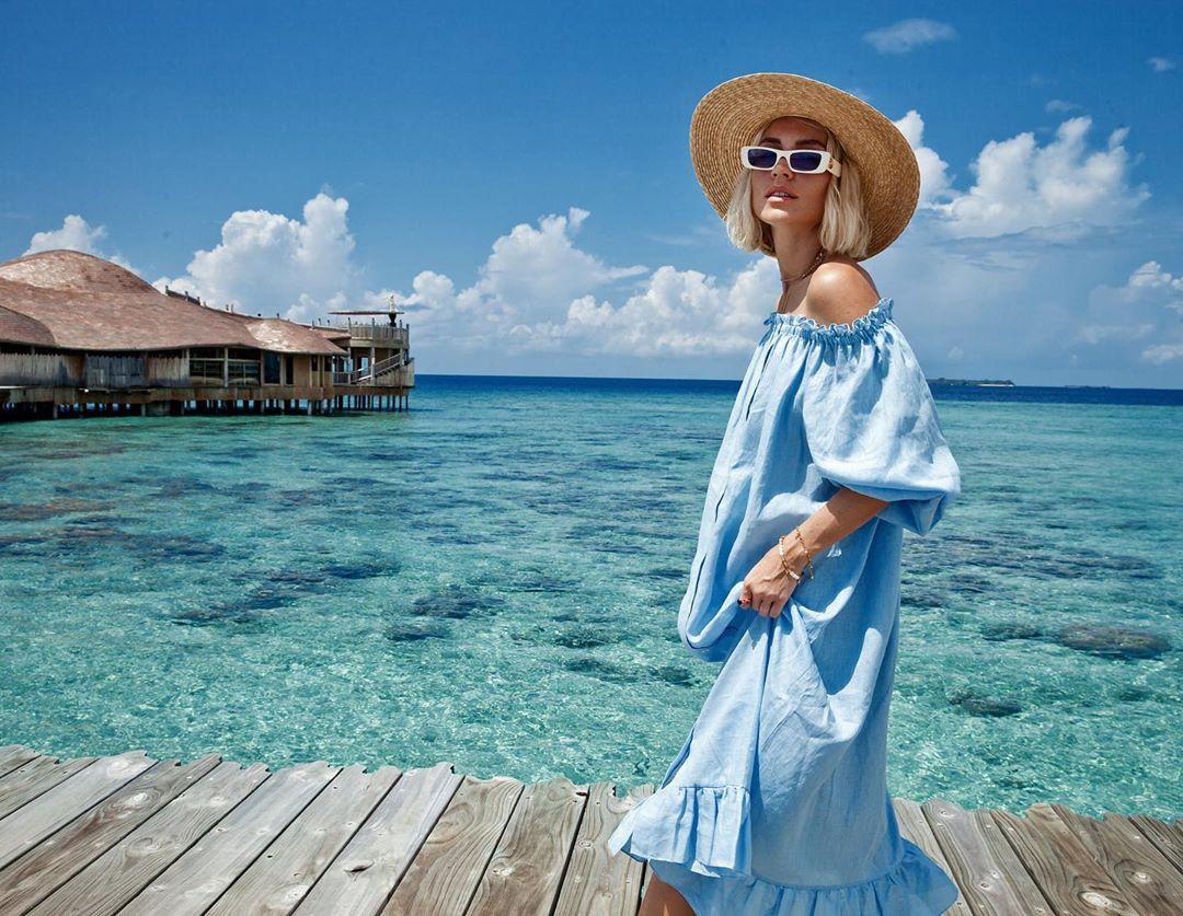 Váy trễ vai phom rộng màu xanh da trời và mũ cói đi biển