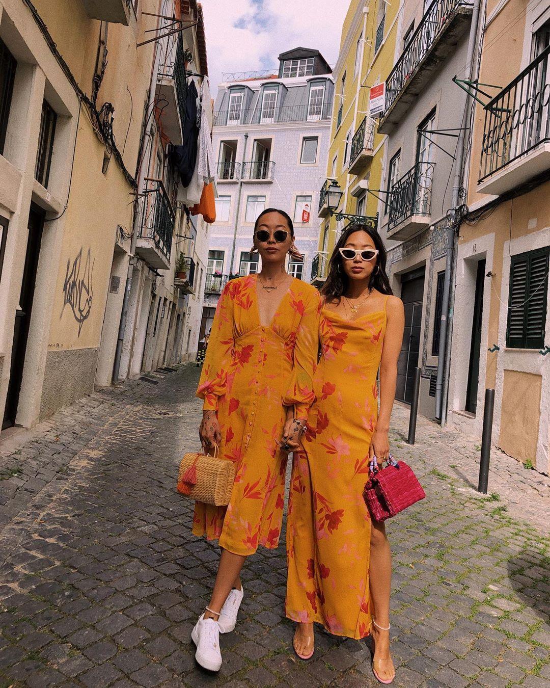 Thời trang cung Song Tử - Chị em Dani và Aimee Song mặc đầm vàng cam in hoa đỏ