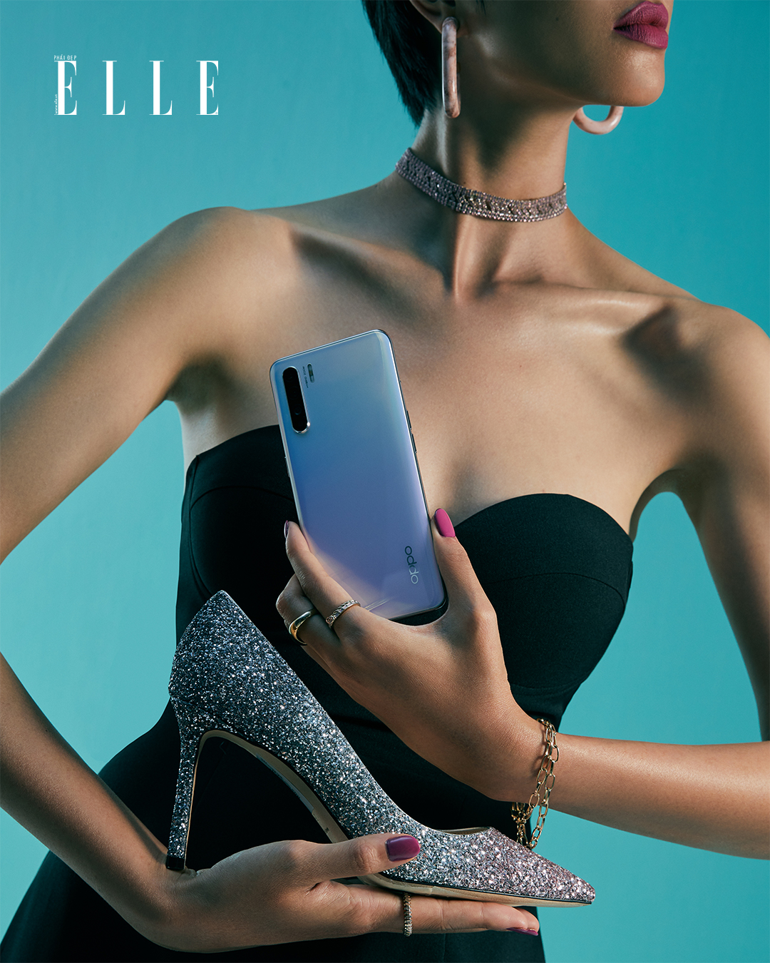 Bộ ảnh thời trang Bản Ngã Thời Thượng - Người mẫu diện đầm đen ôm sát, cầm điện thoại OPPO Reno3 và giày cao gót lấp lánh