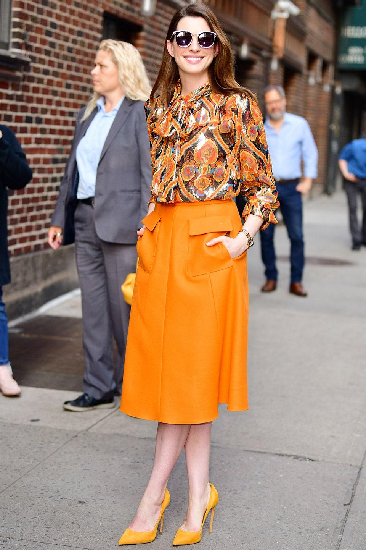 anne hathaway áo sơmi họa tiết chân váy da cam