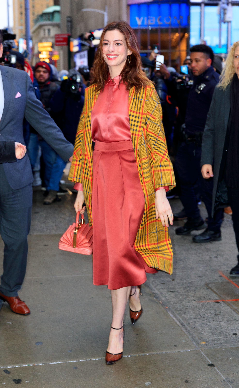 anne hathaway áo sơmi satin chân váy hồng coral áo khoác vàng