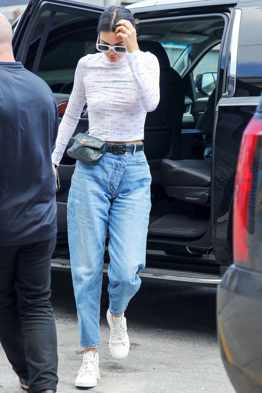 Kendall Jenner mặc áo trắng in hoa, quần jeans baggy và đeo túi thắt lưng Chanel