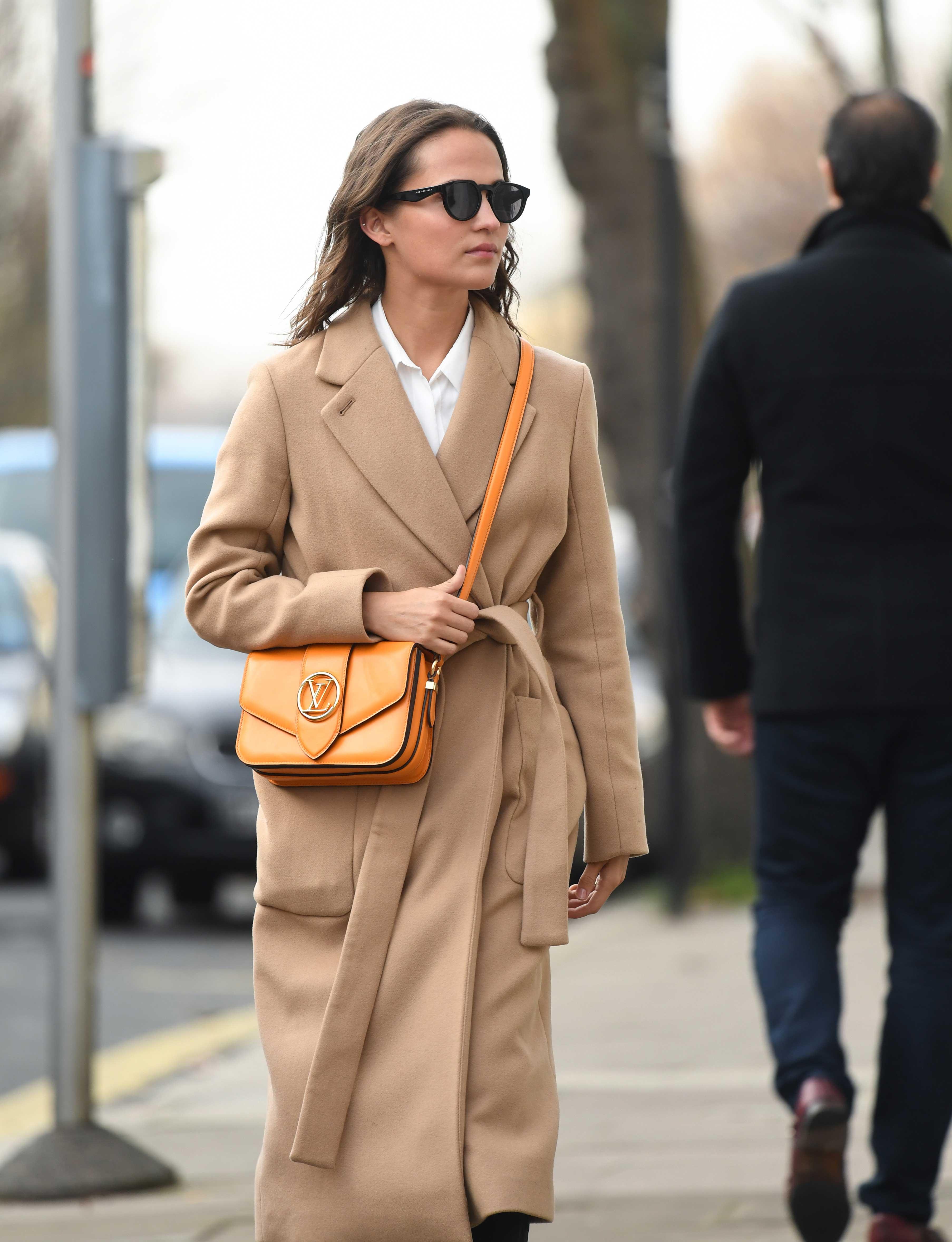 Alicia Vikander đeo túi LV Pont 9 màu vàng cam