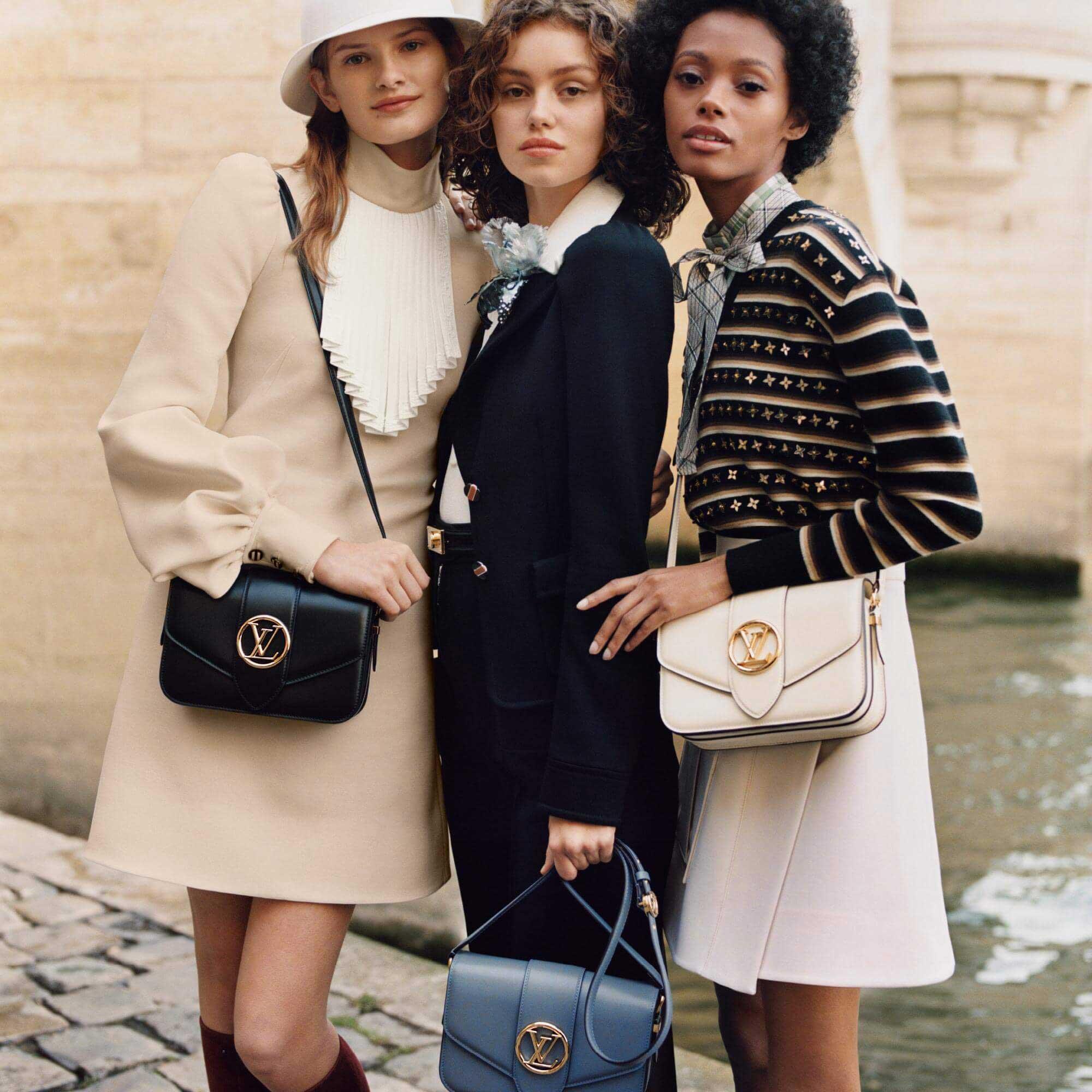 Người mẫu mặc trang phục cổ điển, đeo túi LV Pont 9 màu trắng, đen và xanh