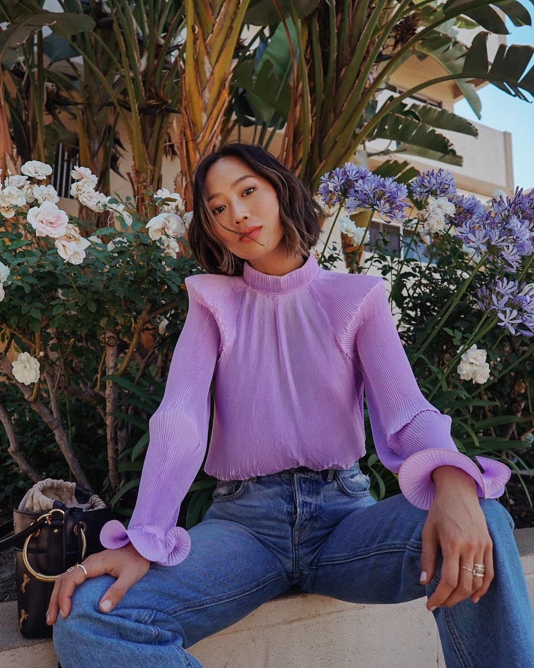 Aimee Song mặc áo sơ mi voan màu tím lilac và quần jeans