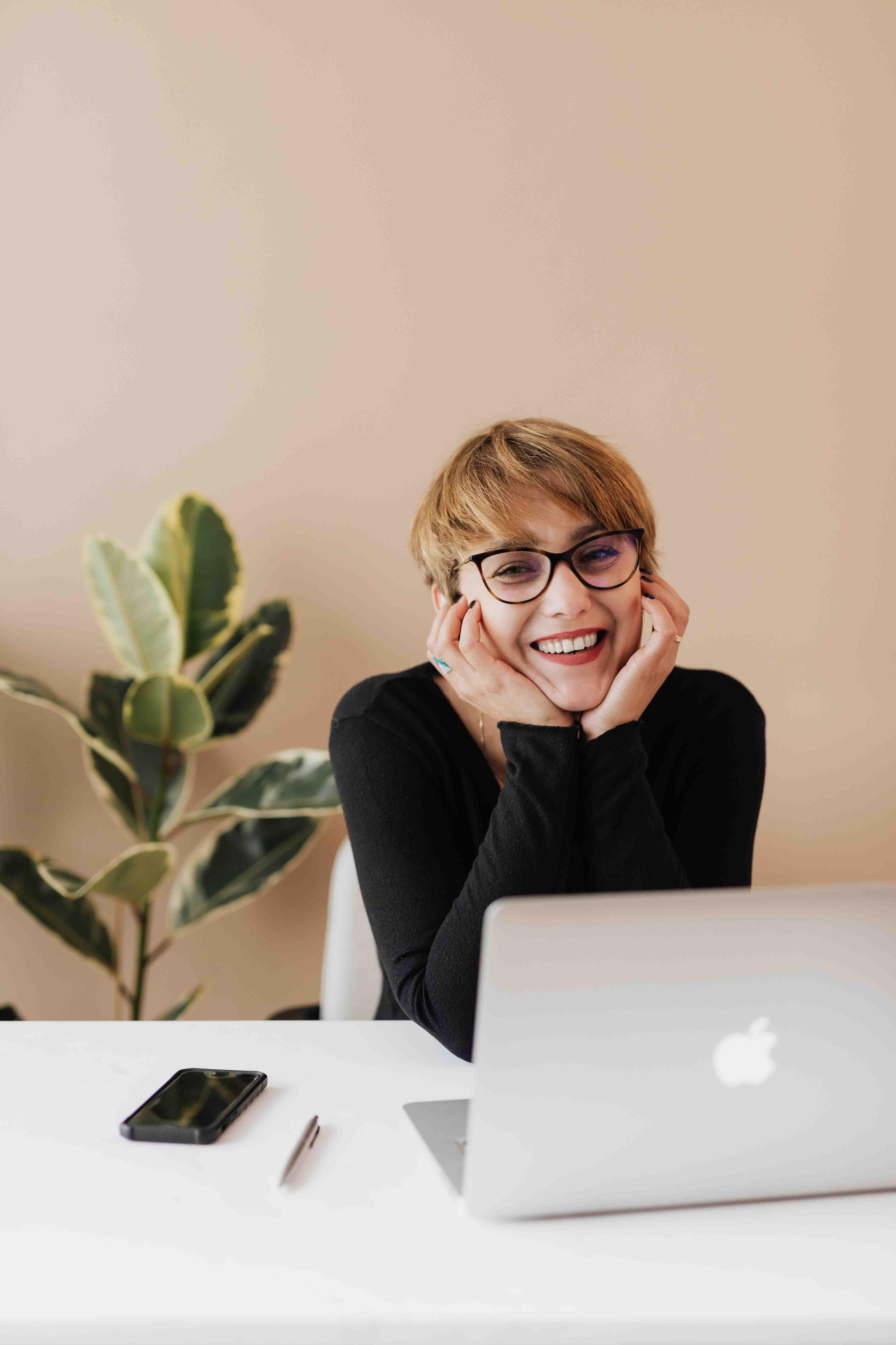 cô gái ngồi cười trước máy tính