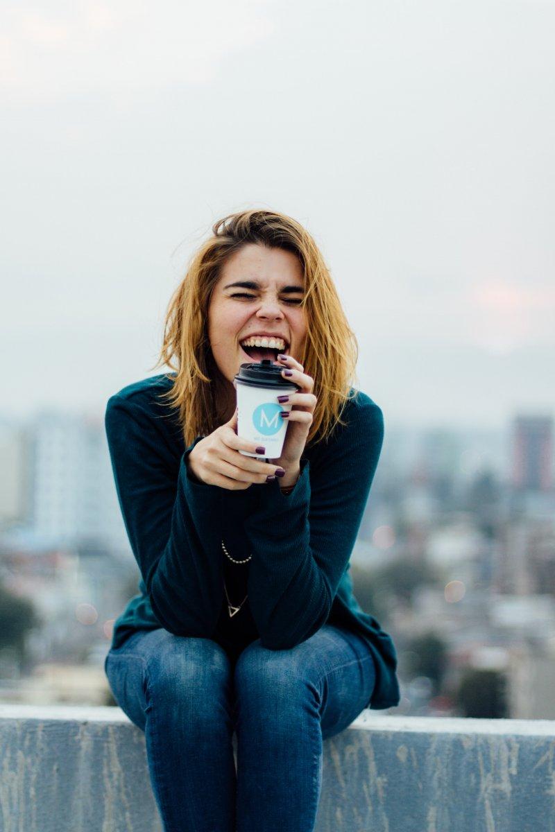 cô gái uống cà phê cười