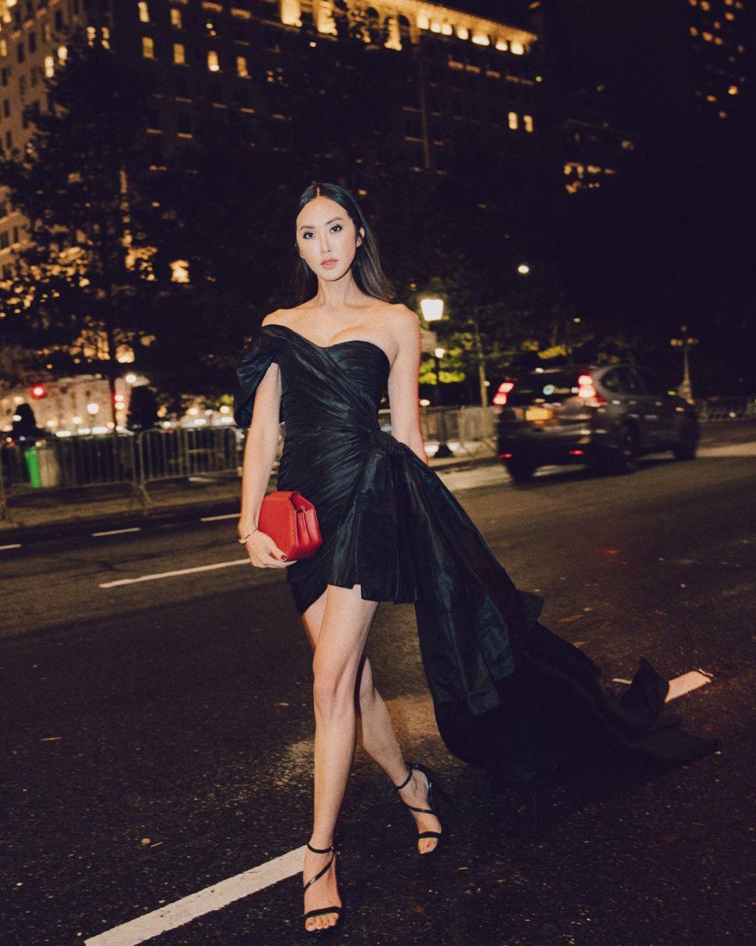 Chriselle Lim mặc đầm đen cầm túi xách đỏ
