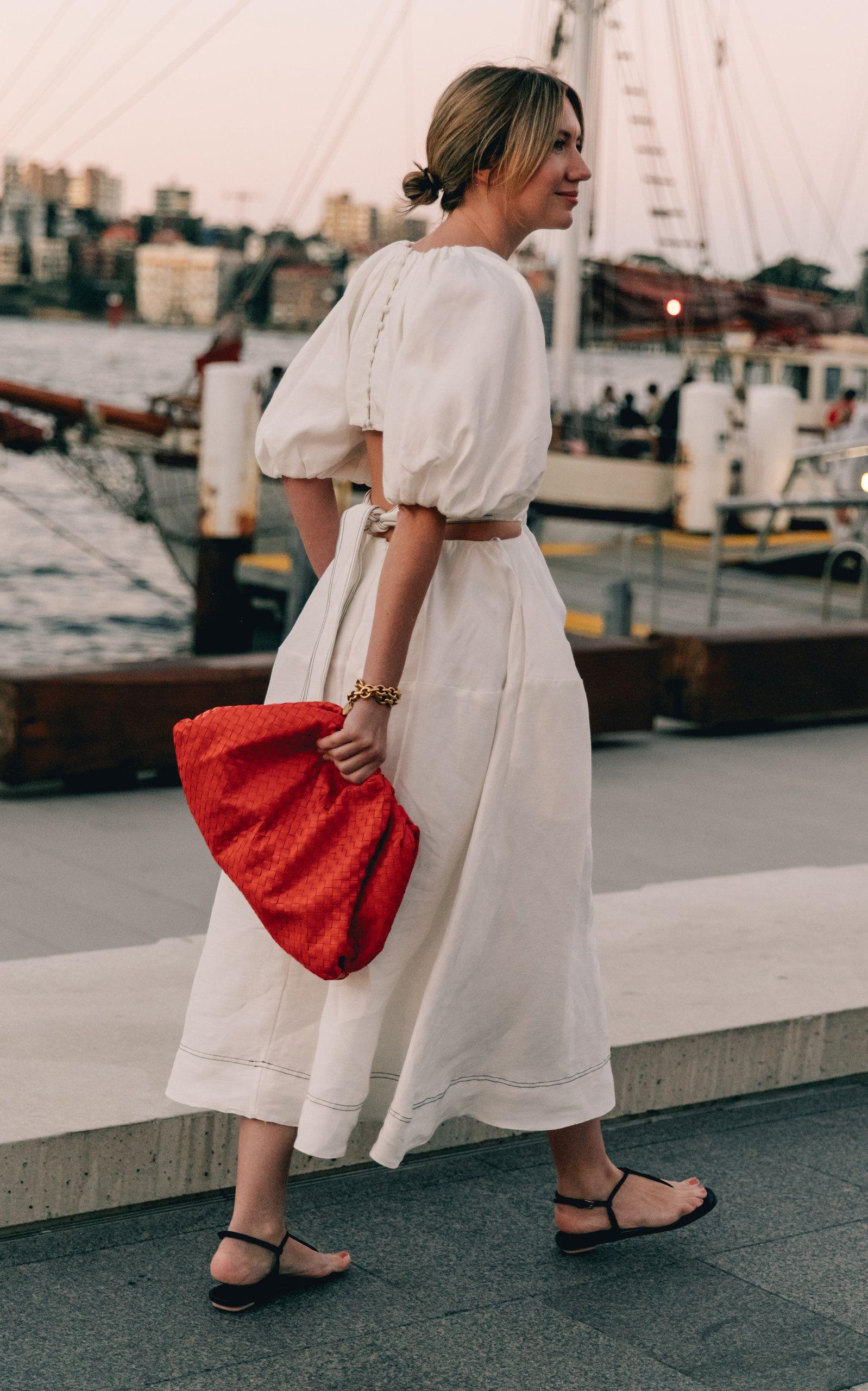 Túi xách đỏ cầm tay và đầm phồng trắng