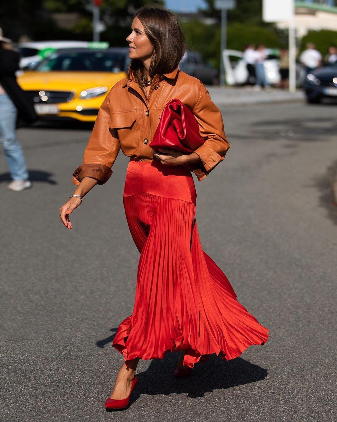 Túi xách đỏ cỡ lớn cầm tay, chân váy xếp ly đỏ