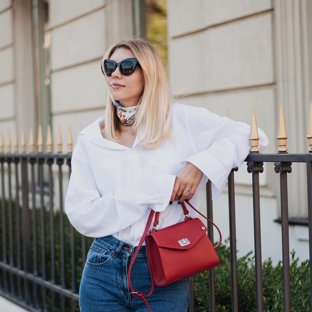 Túi xách đỏ dạng hộp cổ điển và áo sơ mi trắng, quần jeans