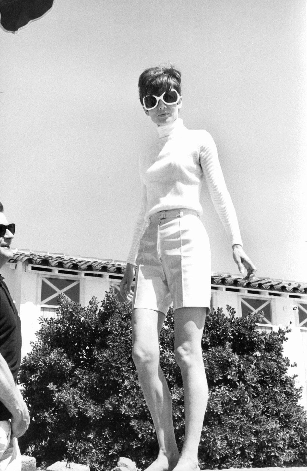 Thời trang Hè - Audrey Hepburn mặc áo len cao cổ, quần bermuda và kính râm to bản