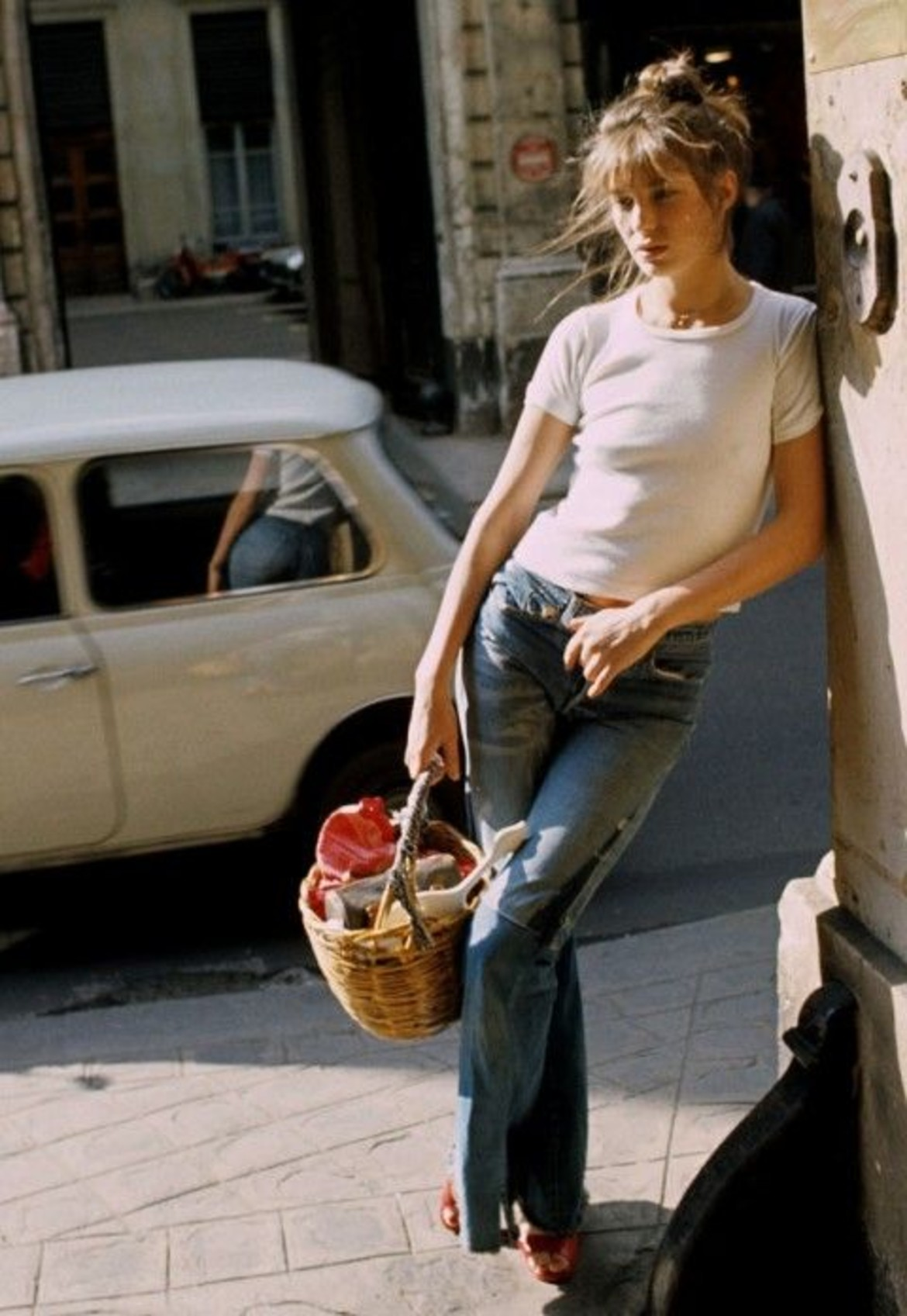 Thời trang Hè - Jane Birkin mặc áo thun trắng quần ống loe và xách túi cói