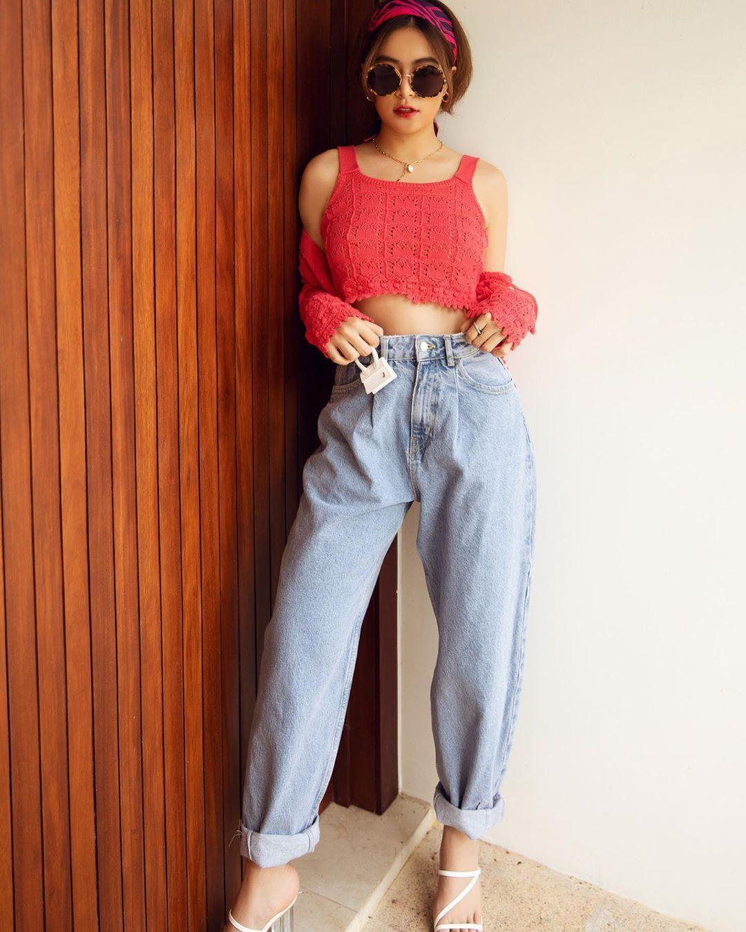 hoàng thùy linh mặc áo hai dây bản to màu hồng và quần jeans