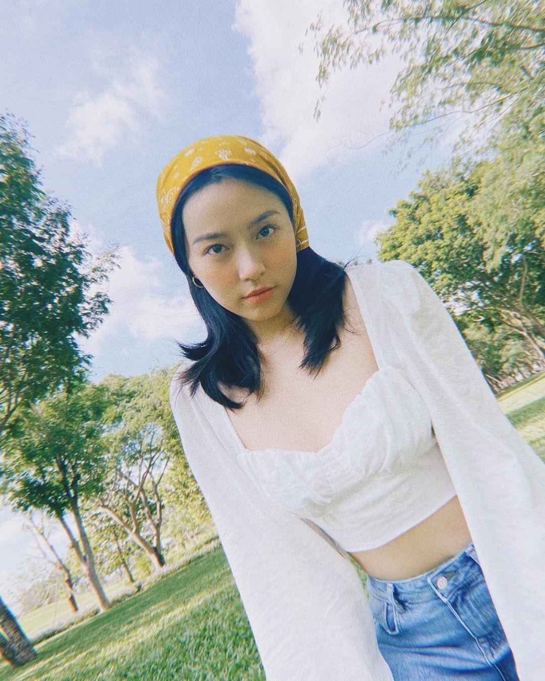 Lê Hà Trúc mặc áo trắng quần jeans quấn khăn bandana vàng