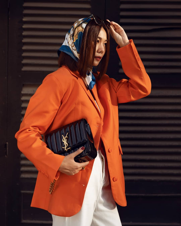 Thanh Hằng mặc blazer cam quấn khăn bandana xanh