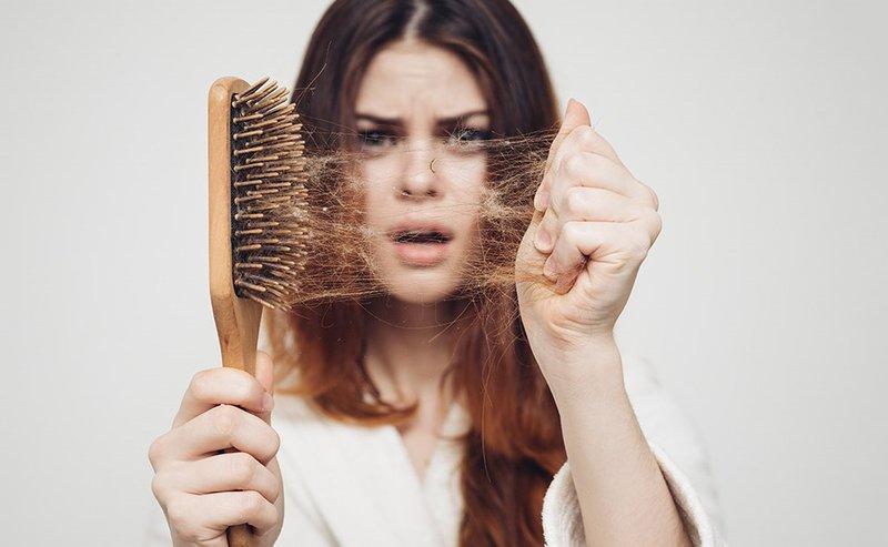Cô gái bị tóc rụng, khó chịu.