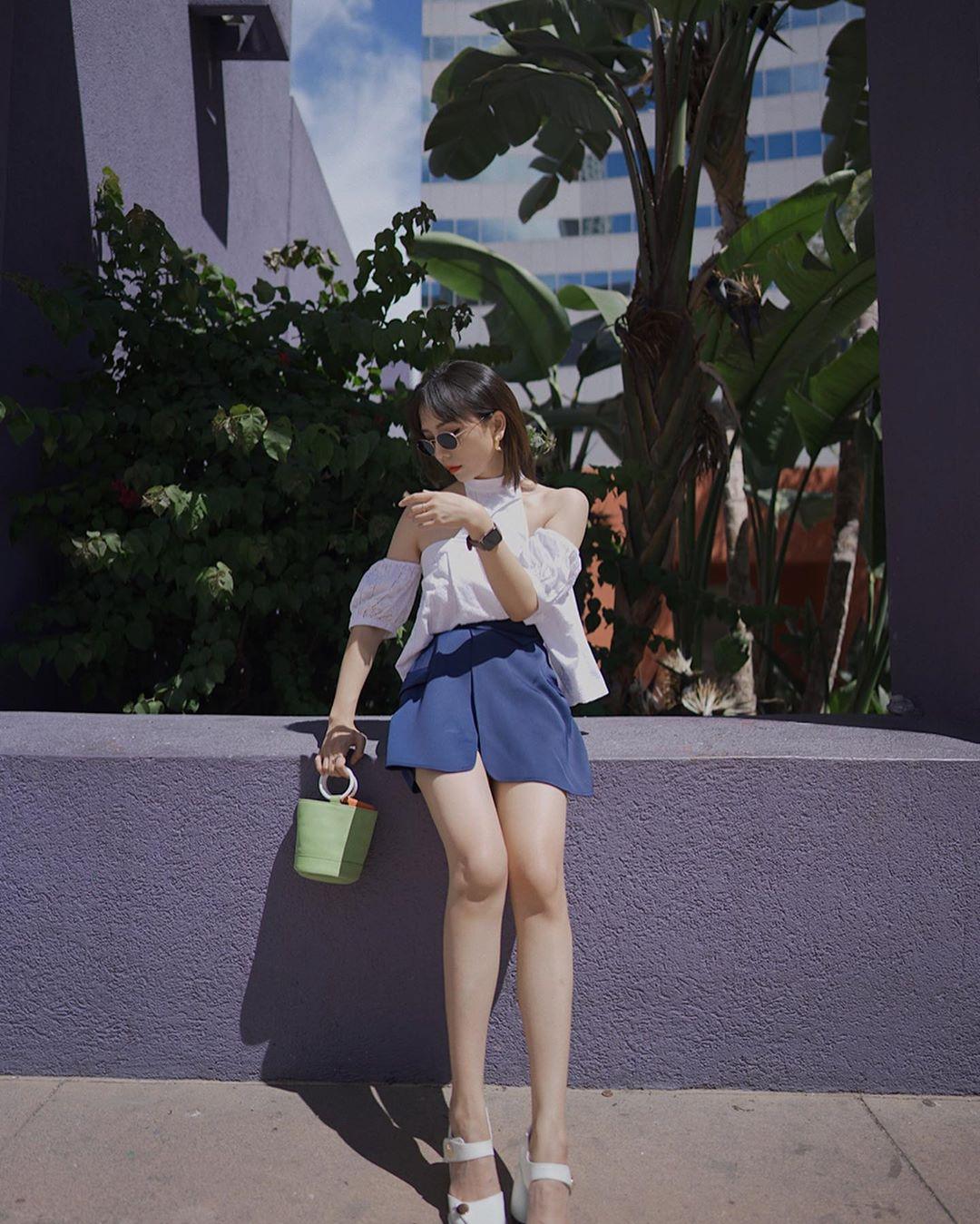 Áo yếm tay phồng màu trắng phối cùng quần shorts xanh