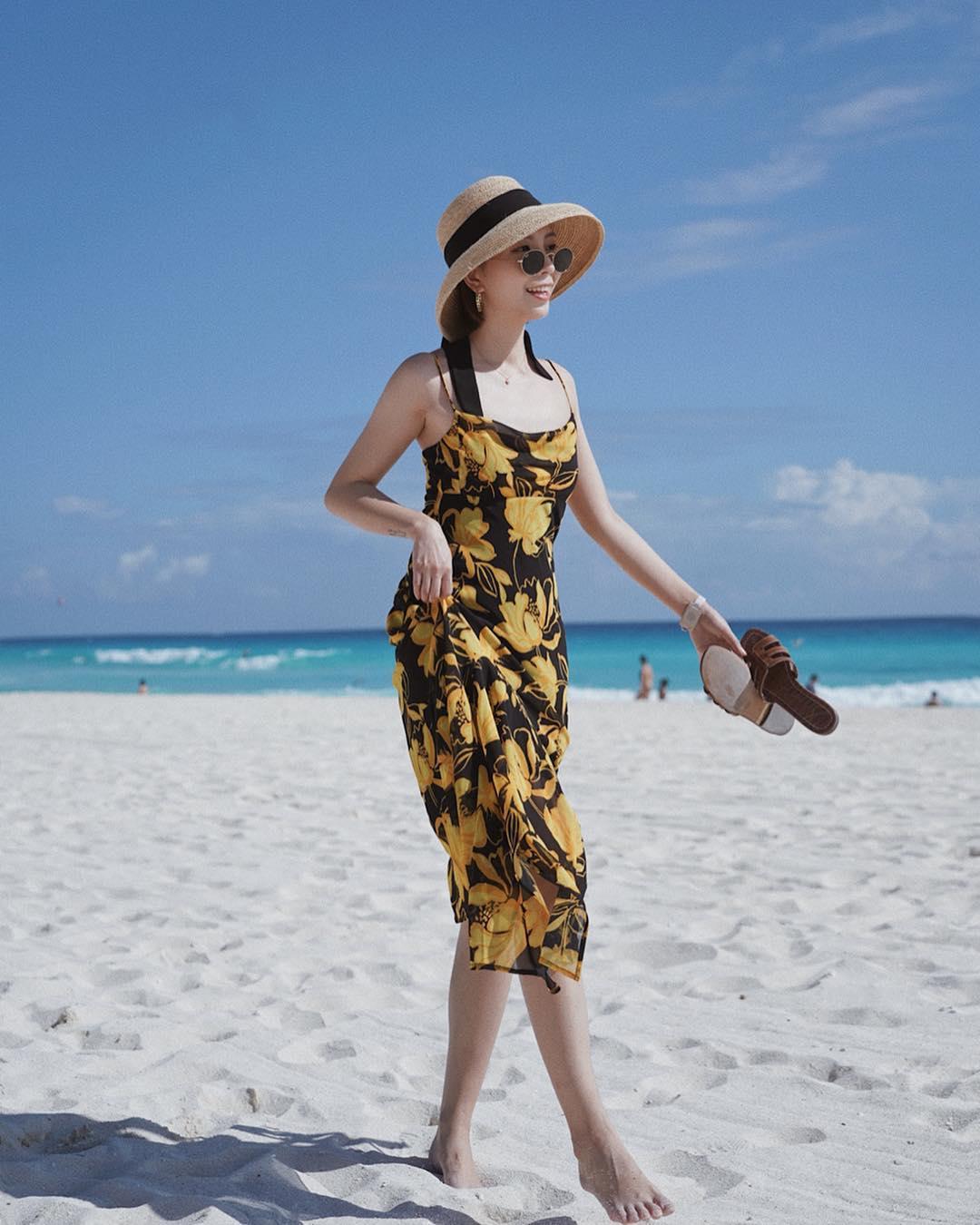 Đầm hai dây in hoa màu đen và mũ cói đi biển