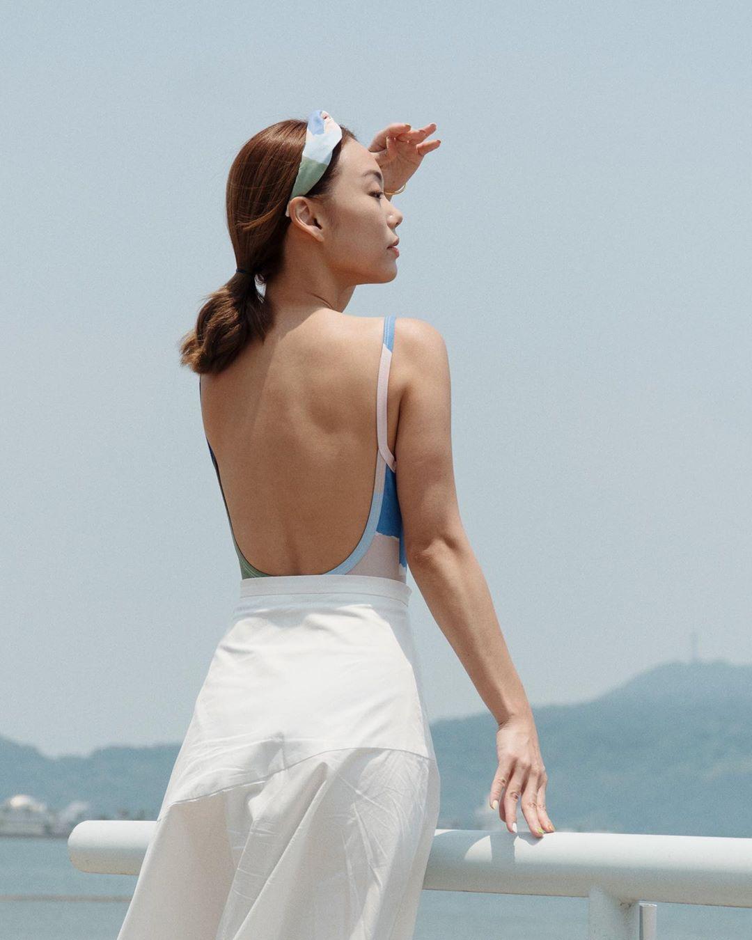 Adrea Chong mặc bodysuit hở lưng và chân váy trắng